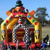 Kids around clown jumping castle image